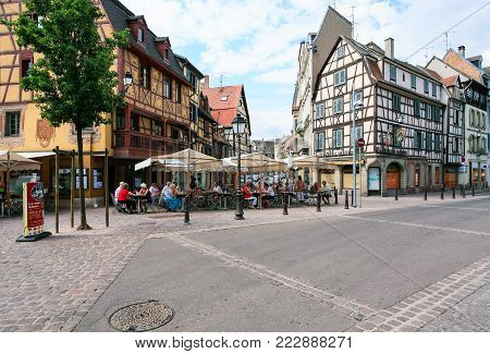 COLMAR, FRANCE - JULY 11, 2010: people in outdoor cafe on square Place des Martyrs de la Resistance in Colmar. Colmar is the third-largest commune of Alsace region