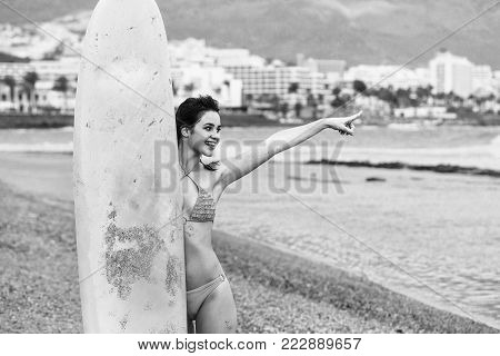 Pretty Happy Girl Surfer With Yellow Surfboard Points Finger