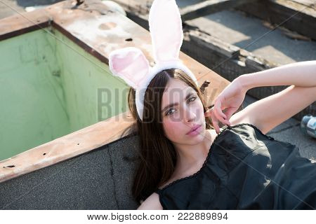 Easter girl lying on grey asphalt background. Woman wearing rosy bunny ears on sunny day. Fashion model with makeup on cute face and long brunette hair. Easter holiday celebration concept