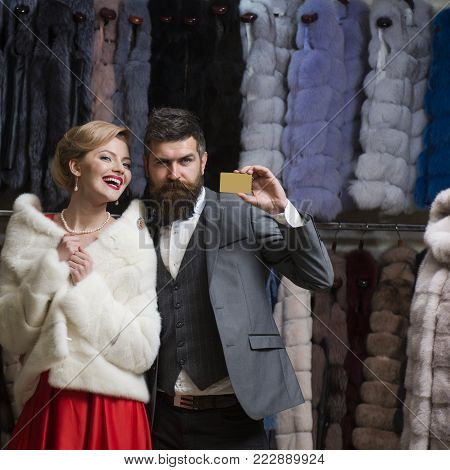 Credit, save, shopping. Date, couple, love, man and woman. Fashion and beauty, winter, fur. Woman in fur coat with man, seller, customer. Couple in love at fur coat, luxury. Business, moneybags.
