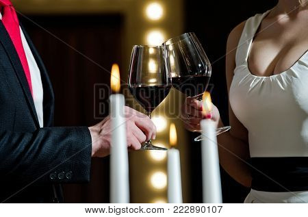couple clink glasses with red wine at meeting or date in formal outfit in restaurant, celebration and relax, bar party, sommelier, tasting and degustation, wedding and anniversary, partnership
