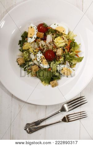 salad dish with croutons, cherry tomatoes, boiled egg quarters and dried parsley on a white plate