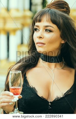 Girl with long brunette hair in black lace bustier. Woman holding glass of wine outdoors. Cocktail party or holiday celebration. Drinking alcohol concept. Bad habit and addiction.
