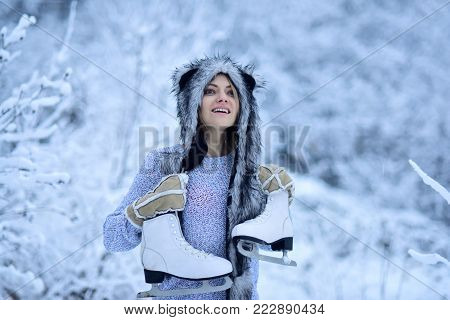 Vacation, holidays, hobby, lifestyle. Happy girl smile with figure skates at trees in snow. Sport, activity, health. Woman with skating shoes in winter clothes in snowy forest. Ice skating concept.