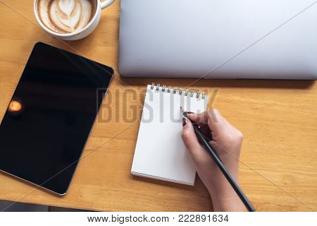 Top view image of a woman's hand holding pencil to writing on blank notebook with tablet , laptop and coffee on wooden table in office