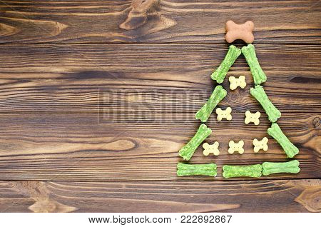 christmas tree made from canine chewing bones and cookies on wooden background poster
