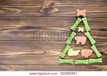 christmas tree made from canine chewing bones and cookies on wooden background