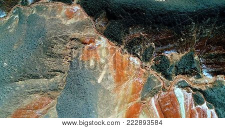 Rainbow mountains - amazing pattern created by nature. Aerial top down view on colorful sandstone hills covered with sparse vegetation in Zhangye Danxia landform geological park in Gansu province, China.