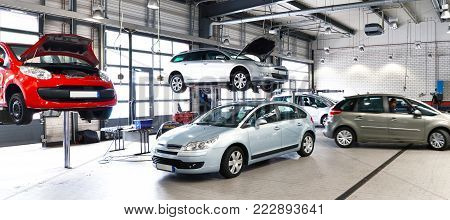 Vehicles In A Car Repair Shop For The Repair With Lifting Platform