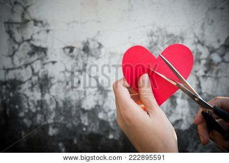 Broken red heart cut by scissor in woman, lady or female hands over cracked dark grey old grunge wall copy space showing strong emotion of sad failed love on Valentine's day, love relationship concept