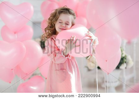 A little girl of 6 years with long curly hair, dressed in a pink dress and white tights.