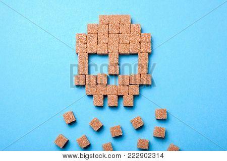 A lot of sugar kills people. Skull of cubes of cane brown sugar.