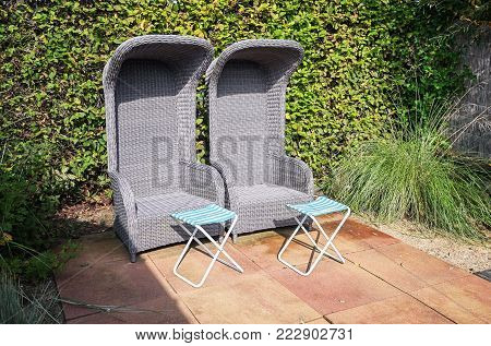 Two rattan garden armchairs with footbed to relax in the garden