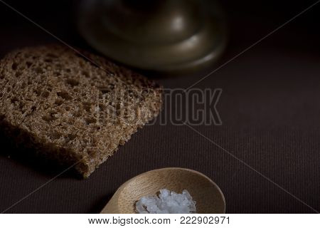 piece rough rye bread with coarse salt on a wooden background still life