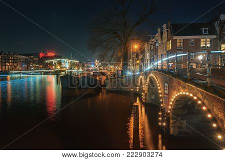 Amsterdam, Netherlands, December 16, 2017: The Magere Bridge over the river Amstel with in the background the characteristic canals buildings in the old center of Amsterdam.