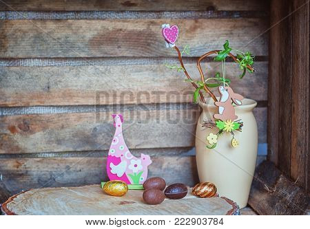Easter composition of Easter eggs, a wriggle hazel with rabbit and heart and an artificial chicken