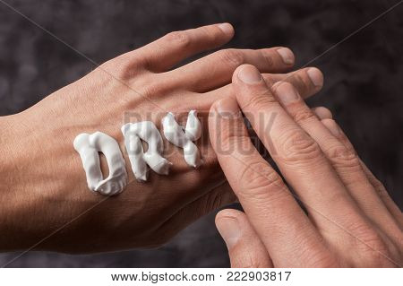 The word Dry is written in cream. Dry hands of a man in cream or ointment. Gray background