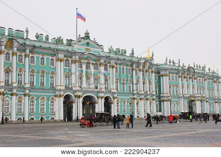 Winter Palace (Hermitage Museum) and Palace Square in Saint-Petersburg, Russia. Historical Downtown Architecture Buildings on Winter Time with Tourists and Main Entrance to Winter Palace Building.