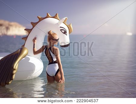 Young pretty fashion woman standing on sea shore beach near resort hotel with giant inflatable unicorn pegasus float mattress in white bikini