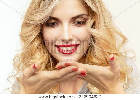A transparent contact lens in the hands of a beautiful blonde who is preparing to insert it.