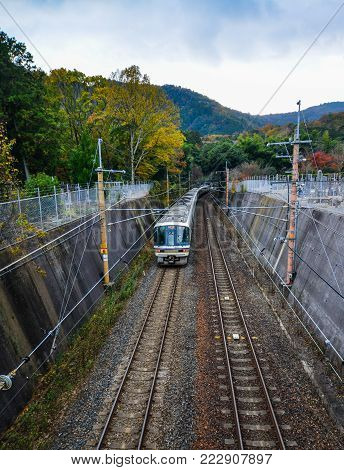 Kyoto, Japan - Nov 28, 2016. A train running on rail track at countryside in Kyoto, Japan. Rail transport in Japan is a major means of passenger transport.