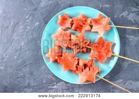 Watermelon in the form of stars on skewers lies on a plate. The blue dish is like a rocket in space. Top view