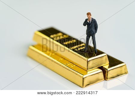 Miniature figure businessman standing and thinking on shiny gold bullions ingot as finance fund manager, investment and wealth concept.