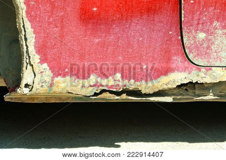 Damaged car. Rusty red car with damaged metal on the floor by rust and holes