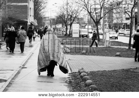 Homelessness. Poor homeless person or refugee covered with blanket walking or wander on the urban street of the city on the cold raining day