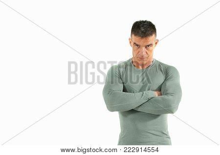 Angry muscular man with muscles in tight shirt and anger in his eyes look in camera isolated on white background