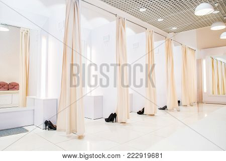 Interior of light dressing room in a female butique. Make Outfit set. Shopping Mall. Shopper. Sales. Shopping Center. Selective focus. Space for text