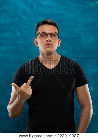 Close-up - young man with glasses shows indecent gesture with middle finger of hand on gray blue background