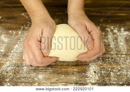 Hands Knead The Dough On Wooden Background