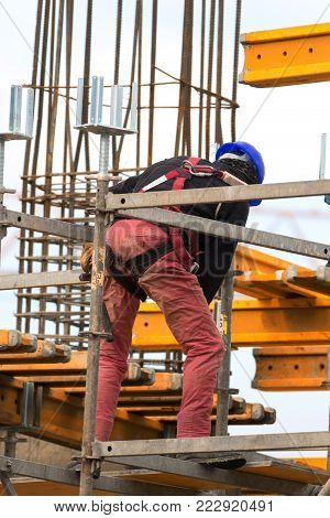 Worker is build metal scaffolding on construction site
