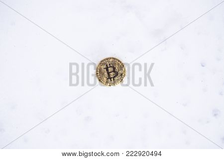 Bitcoin on the snow. Isolated on white background.