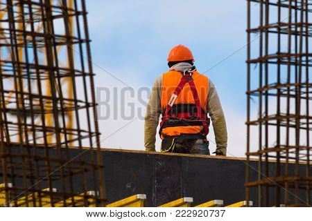 Climber dressed in orange with safety belt on construction site over blue sky