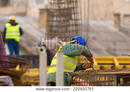Worker repairing the armathure with pliers on construction site