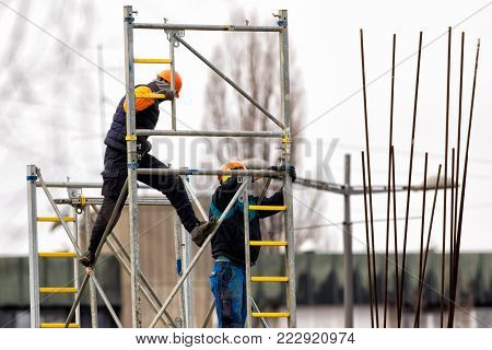 Two builders  build metal scaffolding on construction site