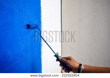 Male hand painting wall in blue with paint roller, New colour