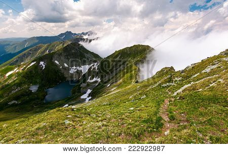 tourist foot path along the mountain ridge. beautiful landscape with lake and rising clouds