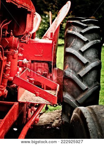 Tractor in field, an old tractor in red on the farm, vintage tractor closeup, large tyres on tractor