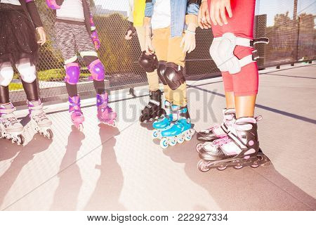 Kids rollerblading on the road with wrist guard, knee and elbow pads