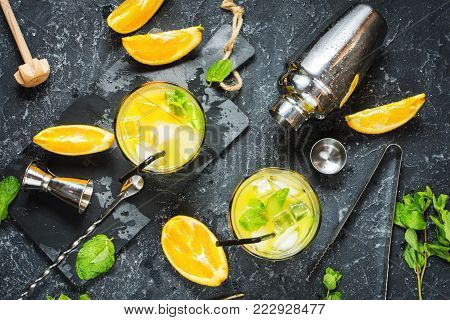 Cold alcoholic summer citrus cocktail with orange and mint in glasses and on dark stone background. Cocktail making bar tools, shaker, glasses, mint leaves. Top view