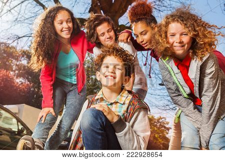 Close-up portrait of smiling teenage boys and girls rollerblading in city at sunny day