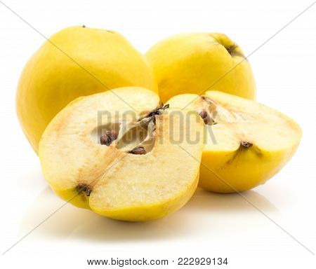 Two yellow quinces with two halves isolated on white background raw ripe one cut in half with seeds inside