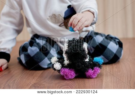 child sculpts a machine from a Velcro constructor on wooden floor indoor