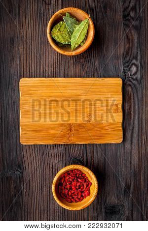 Make menu or write recipe. Mock up for menu or recipe. Wooden cutting board near ingredients in bowls bay leaf and godji on dark wooden background top view.