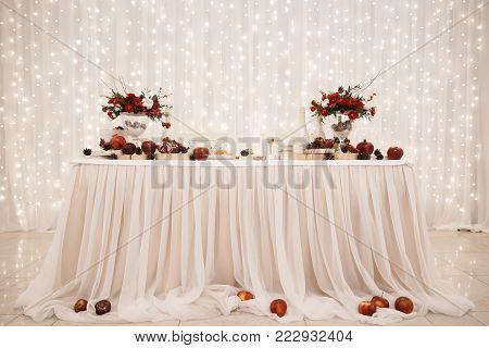 Wedding decorations, a table of the bride and groom, in the background illumination from wedding garlands. Winter Wedding Concept