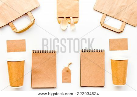 Set of craft bown paper color objects. Paper cup, spoon, fork near paper bag, label and notebook top view mock up pattern.
