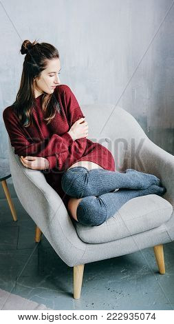 Young adult lonely woman in casual outfit made of bordeaux sweater and kneesocks sitting in grey armchair in minimalist modern interior